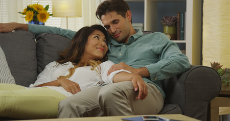 interracial couple: Sweet interracial couple relaxing on couch together Stock Photo
