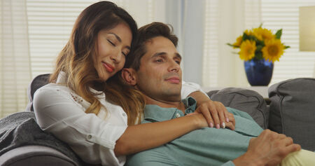 couple on couch: Interracial couple cuddling on couch