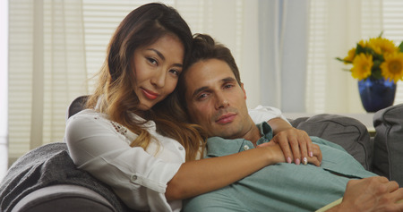 interracial relationships: Attractive interracial couple sitting on couch