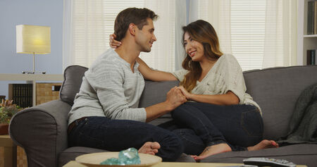 Affectionate mixed couple talking on couch photo