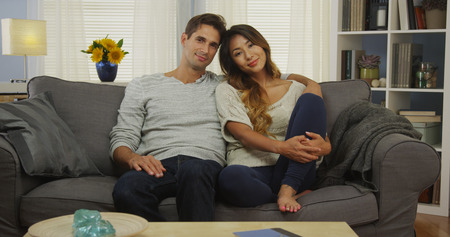 couple on couch: Mixed race couple sitting on couch smiling