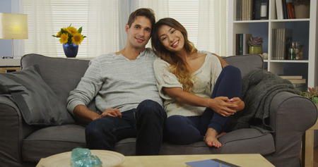 couple on couch: Attractive mixed race couple sitting on couch smiling