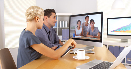 desktop computers: Multi-ethnic business colleagues having a video conference meeting