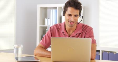 skype: Businessman using headset to talk on the phone