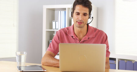 skype: Businessman using headset to talk on the phone