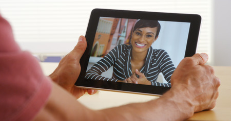 mobile voip: Closeup of attractive african woman talking on tablet