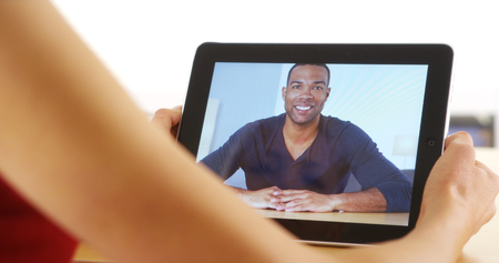 skype: Closeup of casual black businessman talking on tablet