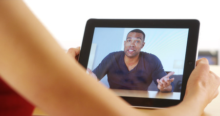 Closeup of casual black businessman talking on tablet