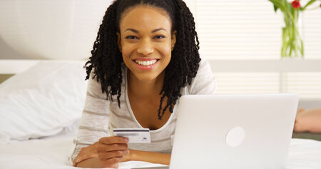 tarjeta de credito: Feliz mujer negro sonriendo con ordenador port�til y tarjeta de cr�dito