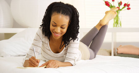 person writing: Young black woman writing in journal