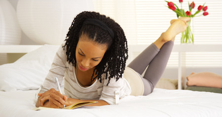 person writing: Happy black woman writing in journal Stock Photo