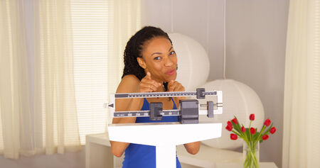 lose balance: Attractive African woman dancing on scales