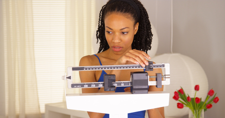 Disappointed black woman checks weight and walks away