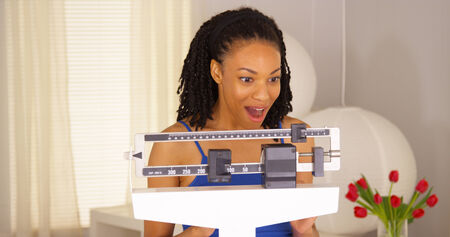 sliding scale: Cute black woman dancing on scales