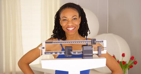 scale weight: African woman feeling very proud of herself