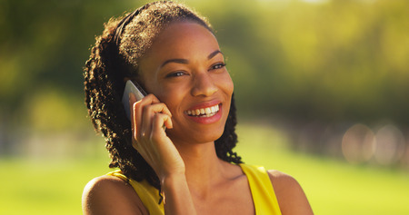 phone: Black woman talking on phone outdoors Stock Photo