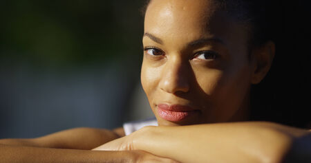 woman resting: Black woman resting on arms looking at camera