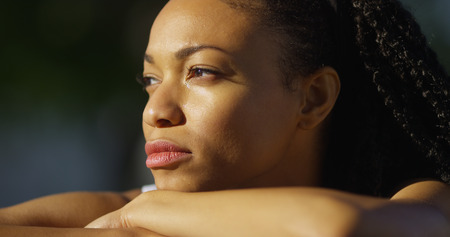 eye's closed: Black woman crying outdoors Stock Photo