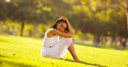 happy african woman: Young African woman sitting in a park