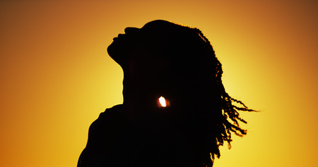 sexy woman standing: Silhouette of African woman standing at sunset