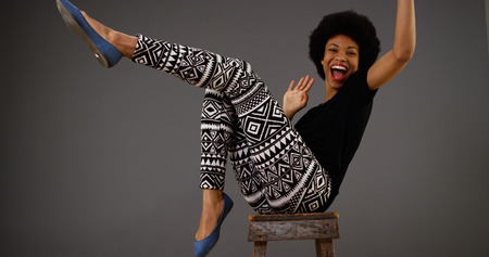stool: Happy black woman dancing on chair Stock Photo