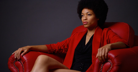african american woman: Strong attractive Black woman sitting in red chair