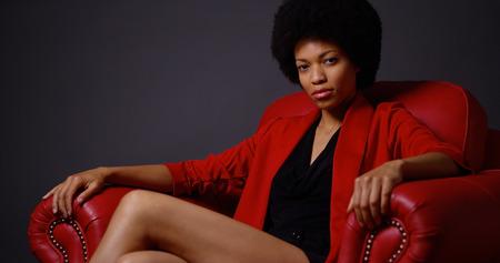Onafhankelijke zwarte vrouw zitten in rode stoel Stockfoto