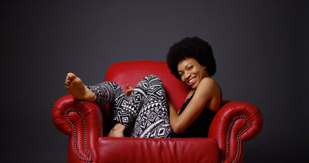 african american woman: African woman sitting in red armchair