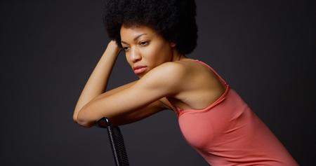 mujer pensativa: Profunda mujer Negro en el pensamiento sentado en la silla