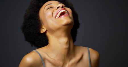 riÃ â  on: Lento sartén encima de la mujer negro ocasional riendo y sonriendo Foto de archivo