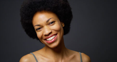 Slow pan up African woman laughing and smiling photo
