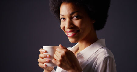 Black woman with afro in studio drinking hot coffee and smiling photo