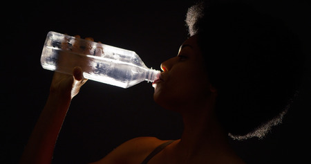 Backlit studio shot of black woman drinking water from bottle