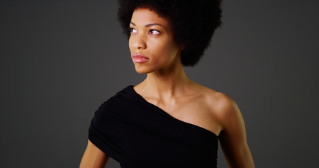 woman black background: African woman in stylish black dress on grey background