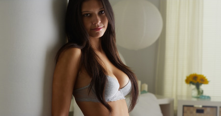 posing: Hispanic woman standing in bedroom in lingerie Stock Photo