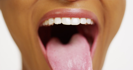 tongue out: Close up of African woman with white teeth smiling and sticking tongue out