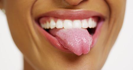 lengua afuera: Cerca de la mujer africana con dientes blancos y sonrisa que pega la lengua hacia fuera