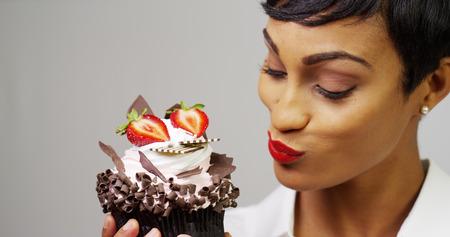Femme noire en admirant un petit gâteau de dessert de fantaisie avec le chocolat et les fraises Banque d'images - 33766369