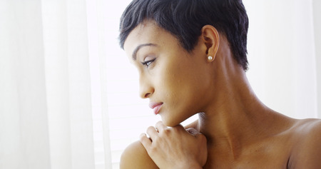 naked black women: Beautiful topless black woman hugging herself and looking out window Stock Photo