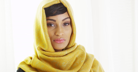 African woman wearing golden head scarf by window photo