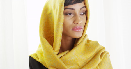 Beautiful African woman wearing gold head scarf in bright room photo