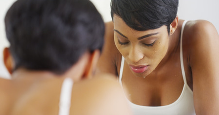 washing hair: Black woman splashing face with water and looking in mirror Stock Photo
