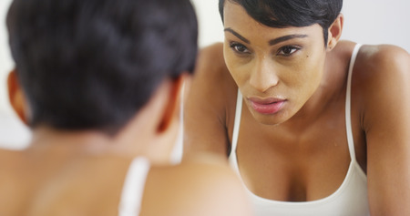 fresh women: Black woman splashing face with water and looking in mirror Stock Photo