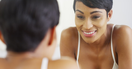 woman mirror: Black woman cleaning face with water and looking in mirror