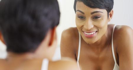 reflexion: Mujer Negro cara de la limpieza con agua y mirando en el espejo
