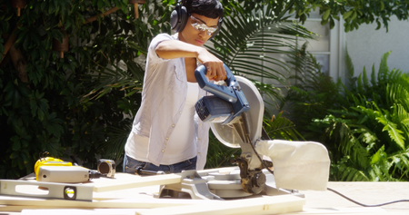 2x4 wood: Black woman doing home improvement cutting wood with a table saw