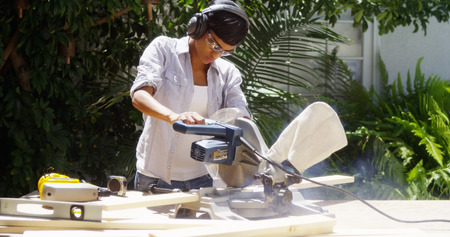 Black woman doing home improvement cutting wood with a table saw 版權商用圖片 - 33805597