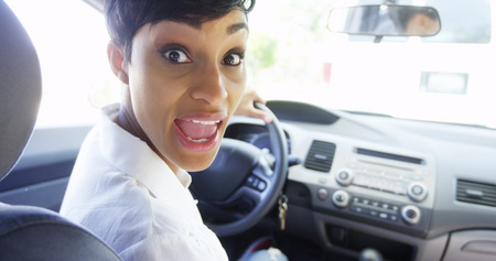 Angry woman in car looking over shoulder and shouting at passenger