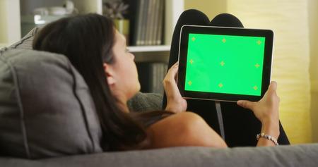 mujer viendo tv: Ni�a de raza mixta que mira la tablilla con la pantalla verde