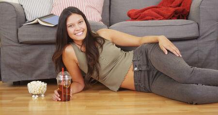 té helado: Mujer hispana acostado en el piso sala de estar con té helado Foto de archivo